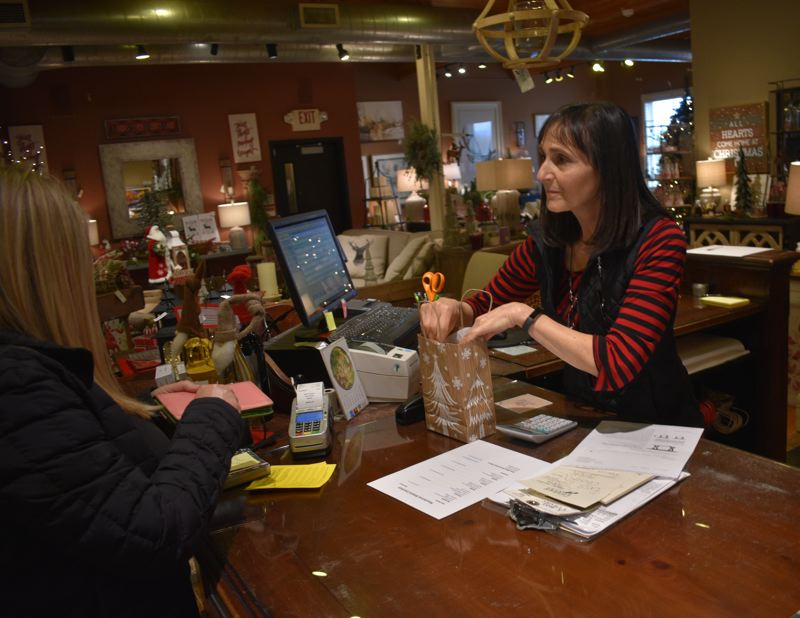 PMG PHOTO: SHANNON O. WELLS - Lillie Lott bags a gift for a customer at Celebrate Me Home/Rustic With a Twist, which owner Mary Greenslade has curated into a holiday shopping wonderland in downtown Troutdale.