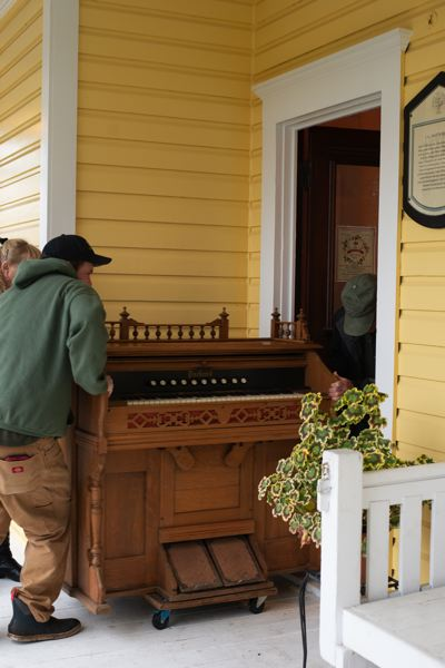 PMG PHOTO: ANNA DEL SAVIO - Volunteers carefully move the organ into the Watts House. The organ is operational, though it hasnt been played in decades.