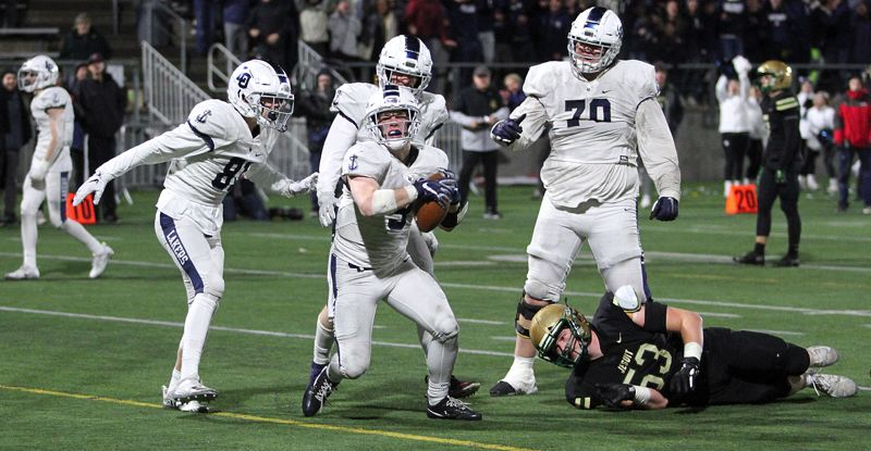 PMG PHOTO: MILES VANCE - Lake Oswego senior running back Casey Filkins (center) exults after scoring the winning touchdown in his team's 28-21 victory over Jesuit in the Class 6A state semifinals at Hillsboro Stadium on Friday, Nov. 29.