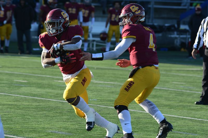 PMG PHOTO: DAVID BALL - Central Catholic QB Cade Knighton hands off to running back Elijah Elliott, who scored three second-half touchdowns and was named the Rams' Outstanding Player.