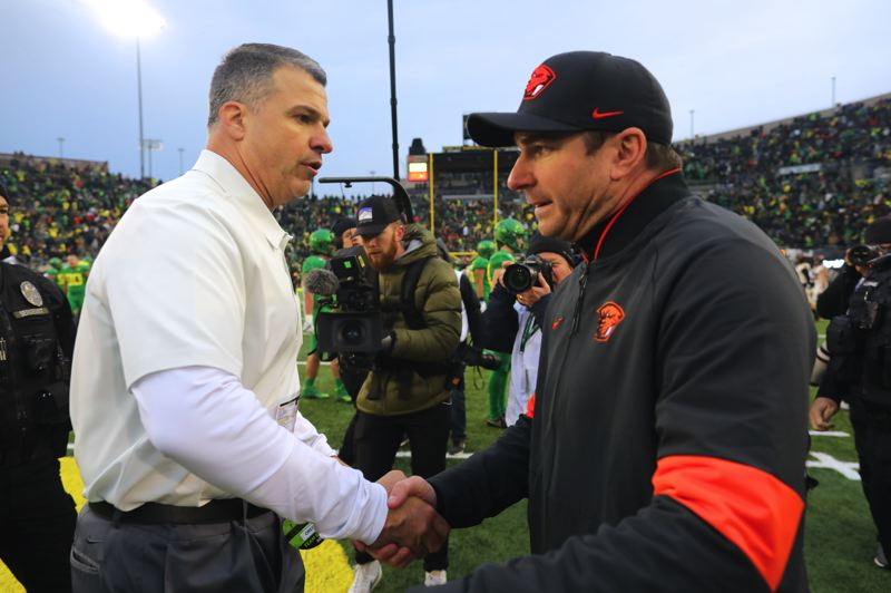 PMG PHOTO: JAIME VALDEZ - Coaches Mario Cristobal (left) of Oregon and Jonathan Smith of Oregon State shake hands after the Ducks' 24-10 victory Saturday at Autzen Stadium.