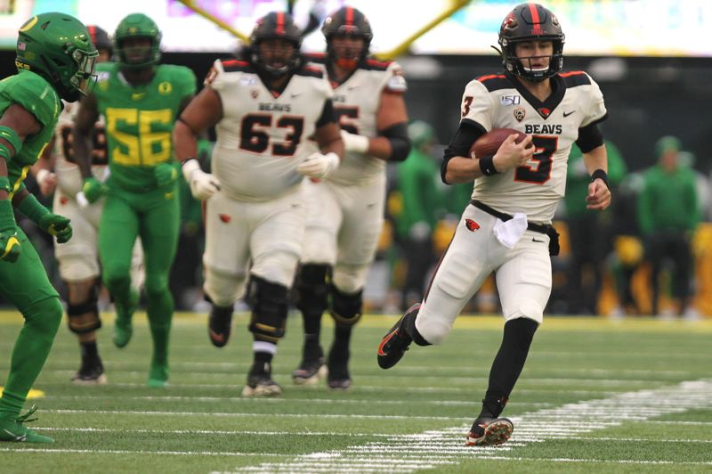 PMG PHOTO: JAIME VALDEZ - Oregon State quarterback Tristan Gebbia (right) runs up the field against the Oregon Ducks in the second half at Autzen Stadium.