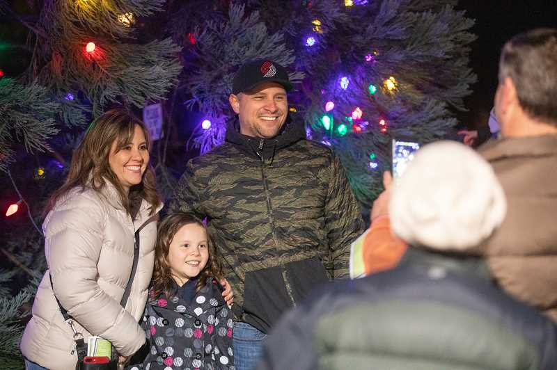 PMG PHOTO: JONATHAN HOUSE - From left, Dolores, Claire and Derek Cranley get a photo in front of the Christmas tree at Millennium Plaza Park.