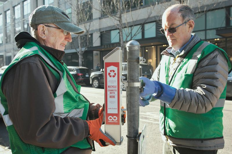 PMG PHOTO: JAIME VALDEZ - John Wertzler, left, and David Mitchell, volunteer members of the Pearl District Neighborhood Association, install a receptacle for cigarette butts on the corner of NW Davis and 11th, outside The Armory Theater join the Pearl District.
