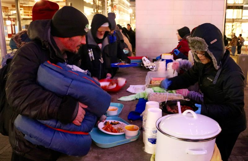 PMG PHOTO: ZANE SPARLING - Hungry people line up for meals served by Free Hot Soup volunteers at Director Park in Portland on Monday, Dec. 2.
