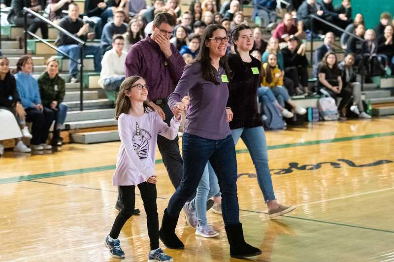 PMG PHOTO: CHRISTOPHER OERTELL - Ellie Dummer (left) and her family are introduced during a Sparrow Club assembly at Tigard High School on Nov. 21. Students are undertaking community service that is matched by donations from Black Rock Coffee to a fund set up for Ellie Dummer.