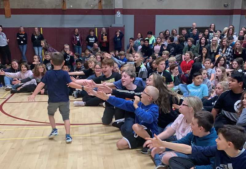 COURTESY OF LAURA QUEEN - Asher, selected as both Sherwood and Laurel Ridge middle schools Sparrow, gets high-fives from students during an assembly in September.