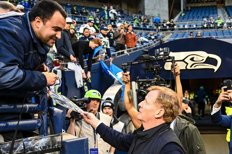 MICHAEL WORKMAN PHOTO - NFL Commissioner Roger Goodell signs an autograph for a fan before Monday night's Seattle-Minnesota game.