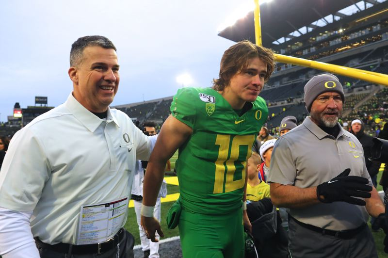 PMG PHOTO: JAIME VALDEZ - All smiles after beating the Beavers, Mario Cristobal (left) and Justin Herbert can celebrate a Pac-12 title if the Ducks' QB returns to his best form in Friday's game against Utah.