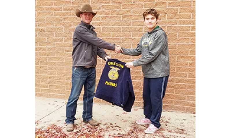 SUBMITTED PHOTO - Jesse Newbill, right, shakes hands with Weston Fowler of Northwest Farm Credit Services, as Fowler presents the freshman FFA member with his new FFA jacket.