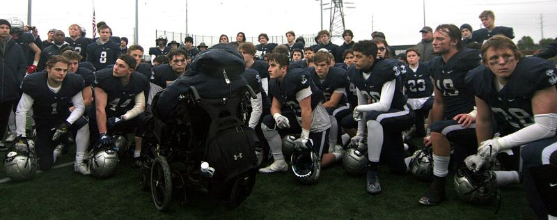 PMG PHOTO: MILES VANCE - Members of the Lake Oswego football team gather around assistant coach Jeff Young's wheelchair following their 49-28 loss to Central Catholic in the Class 6A state football championship game at Hillsboro Stadium on Saturday, Dec. 7.