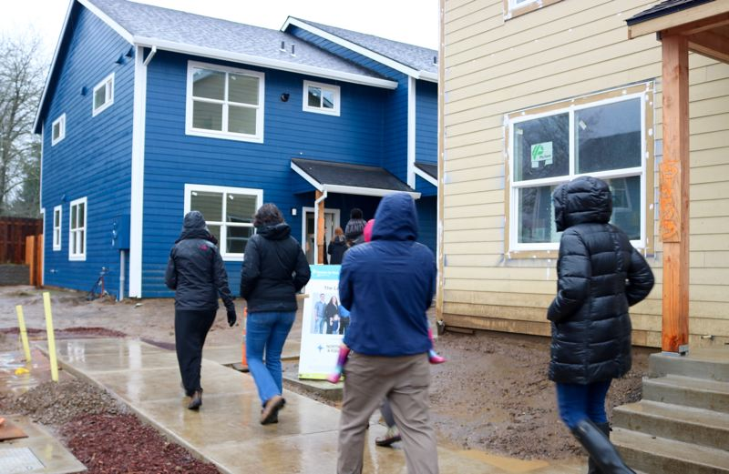 PMG PHOTO: ZANE SPARLING - New homeowners check out the Cully Place development on Northeast Killingsworth Street during a rainy Saturday, Dec. 7, in Portland.