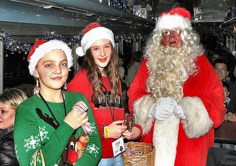 DAVID F. ASHTON - Santas helpers, Caitlyn and Greta, with baskets of candy canes in tow, help jolly St. Nick bring Holiday cheer to everyone on the train.
