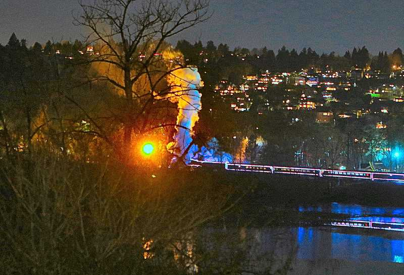 DAVID F. ASHTON - Seen from atop Oaks Bottom Bluff along S.E. 13th, another Holiday Express outing passes beyond of the Oaks Bottom Lagoon, its image reflected in the water - with the West Hills providing the backdrop, beyond the Willamette River.