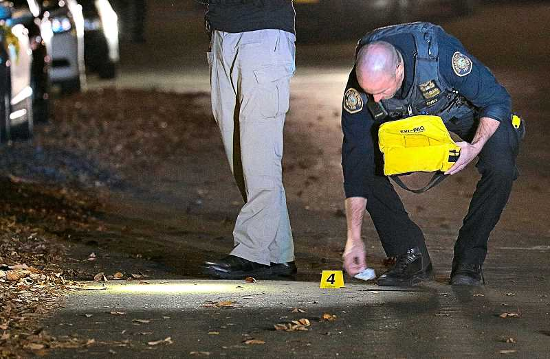 DAVID F. ASHTON - A bullet casing in the middle of S.E. Rhone Street was marked by a Central Precinct officer, as the shooting incident investigation continued.