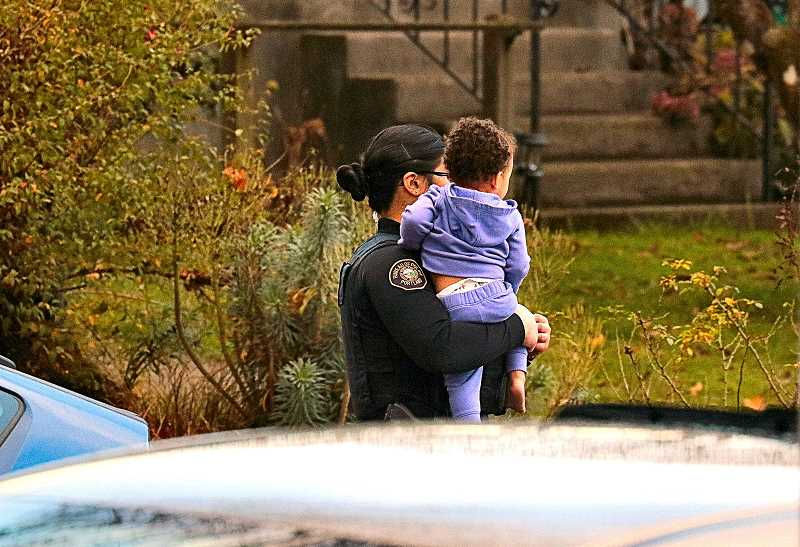 DAVID F. ASHTON - An officer carries one of the involved children, in this domestic violence incident, from the apartment building to safety.