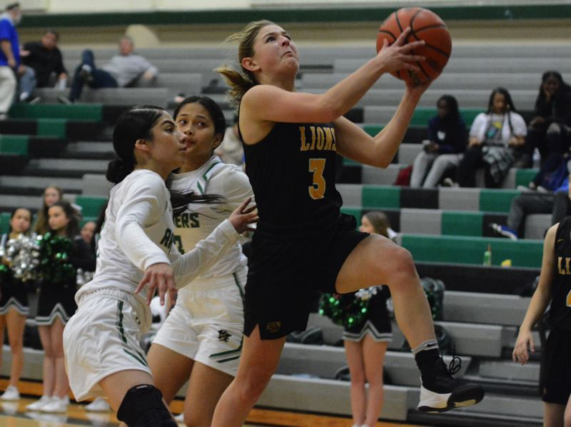 PMG PHOTO: DAVID BALL - St. Helens Maria Reardon closes in on a layup during the Lions 52-25 win at Reynolds on Thursday, Dec. 5.