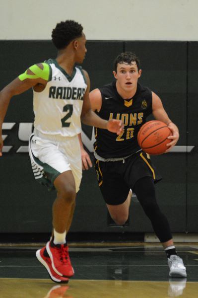 PMG PHOTO: DAVID BALL - St. Helens guard Canon Beisley moves up the floor against Reynolds defender Dominique Miller.