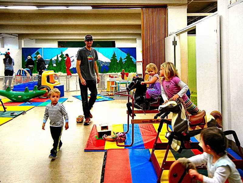 ELIZABETH USSHER GROFF - Southeast Indoor Park volunteer Nate Scott (center) attends with his 2 year old son Thayer (left) and 4 year old daughter Hadley (front right, climbing onto horse) - as toddler Roxy Schaack-Borger rocks on a horse, back right. The colorful Mt. Hood mural was designed and painted in 2016 by Andrea Lawhead.