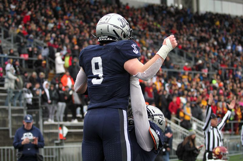 PMG PHOTO: MILES VANCE - The Lake Oswego offensive line — including senior Niko Smith (right) — lifted up senior running back Casey Filkins all year long, doing it literally after Filkins' first touchdown in the Class 6A state championship game.