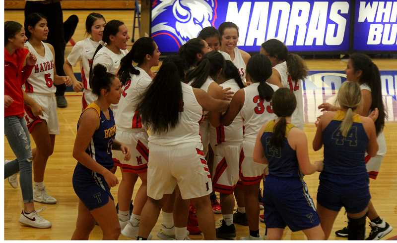 STEELE HAUGEN - The Madras girls basketball team celebrates after Keala Rauschenburg, a player with down syndrome, hits a 3-pointer in the Lady Buffs' 71-27 victory over Toledo Dec. 6.