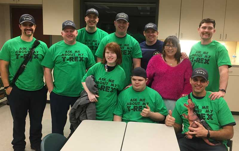PHOTO COURTESY: CLACKAMAS FIRE - Timm Wilson-Kreuger is a big fan of the Tyrannosaurus rex so the firefighters bought matching green shirts along with a large poster of a T-rex.