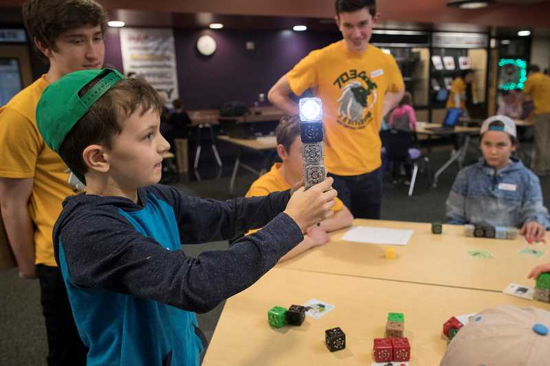 PMG PHOTO: JAIME VALDEZ - Andrew Dagostino, a fourth grader at Trillium Creek Primary School, holds up a Cubelets piece during robotics camp at the high school.