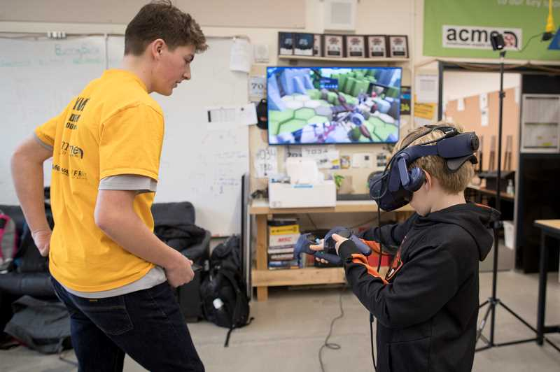 PMG PHOTO: JAIME VALDEZ - Cooper Jordan, a freshman at West Linn High School, watches as Ethan Cannon-Zioko, a fourth grader at Bolton Primary School, play an Augmented Reality game during robotics camp at the high school.