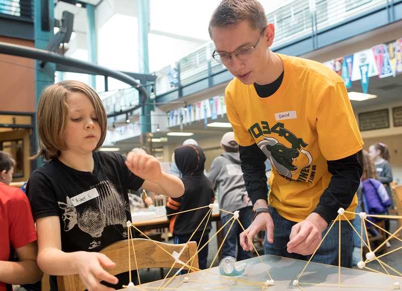 PMG PHOTO: JAIME VALDEZ - Asher Eraut, a second grader at Bolton Primary School, gets assistance from David Olson, a senior at West Linn High School, making spaghetti marshmallow display during robotics camp at the high school.