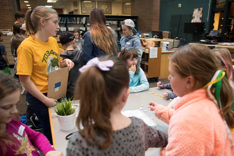 PMG PHOTO: JAIME VALDEZ - Kate Sousley, a sophomore at West Linn High School, talks with elementary students during robotics camp at the high school.