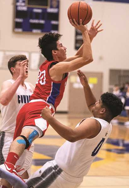 LON AUSTIN/CENTRAL OREGONIAN - Abel Nunez takes a charge from Dylan Heath of Madras. The Cowboys defeated Madras 88-43 Tuesday night to improve their record to 2-1.