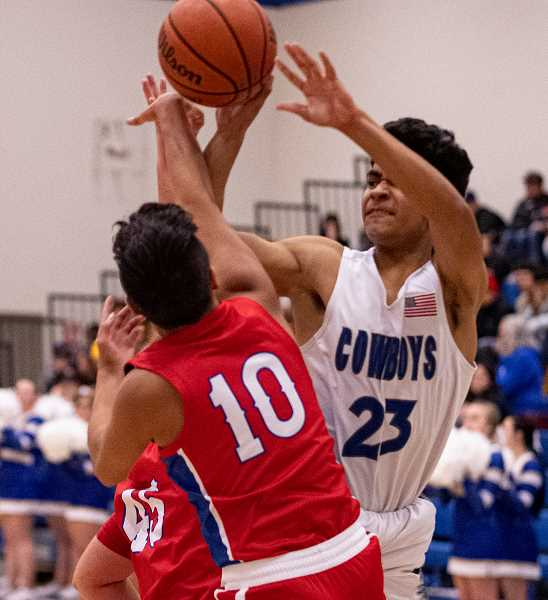 LON AUSTIN/CENTRAL OREGONIAN - Kevin Sanchez is fouled on his way to the basket. Sanchez, who led the Cowboys in scoring on Saturday with 23 was held to just five points by Madras on Tuesday, but it didn't matter as the Cowboys rolled to an 88-43 win over the White Buffalos.