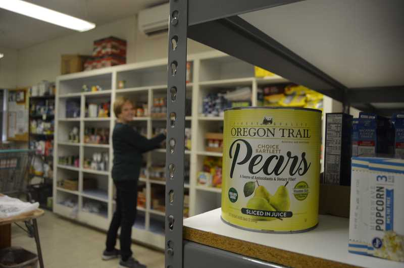 PMG PHOTO: MARK KIRCHMEIER - Volunteer Rosemary Bisner stocks food at the St. Vincent de Paul food pantry in Scappoose.