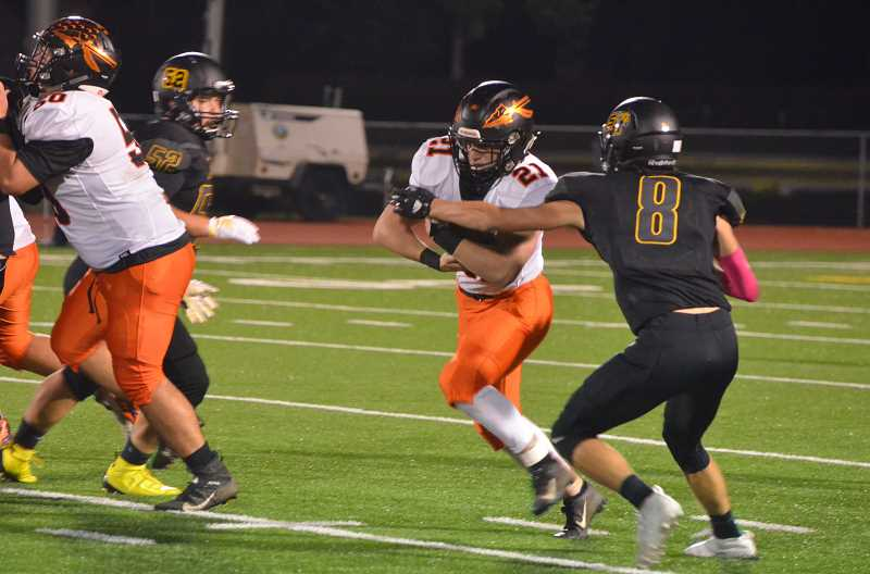 COURTESY PHOTO: JOHN BREWINGTON - Scappoose High junior Deacon Smith carries into the line against St. Helens as Adam Stockwell (right) goes for a tackle.