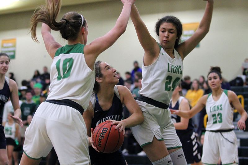 PMG PHOTO: MILES VANCE - West Linn's Olivia McVicker (left) and Audrey Kehoe surround Wilsonville's Angela Morris during the Lions' 82-51 win at West Linn High School on Friday, Dec. 13.