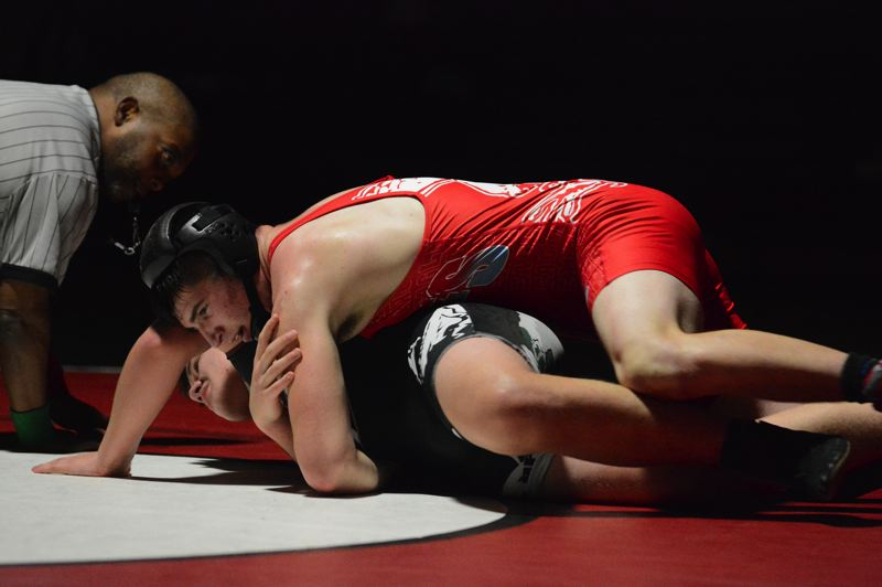 PMG PHOTO: DAVID BALL - Centennials Gabe Steen finishes off his winning takedown for a 6-4 overtime win at 220 pounds.