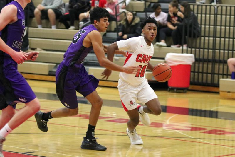 PMG PHOTO: JIM BESEDA - Clackamas guard K.J. Horsley (10) drivers around South Eugene's Josh Paul during the first half of Saturday's 67-42 non-conference boys basketball victory over the Axe at Clackamas High School.