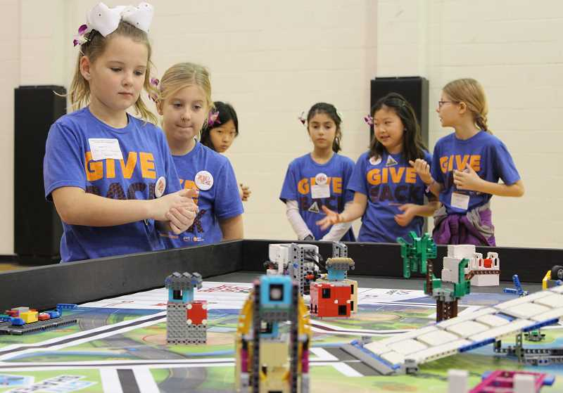 PMG PHOTO: ASIA ALVAREZ ZELLER - 'Invention' watches expectantly as their robot moves along the game table to complete missions.