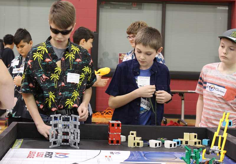 PMG PHOTO: ASIA ALVAREZ ZELLER - West Linn's 'Beach Chickens' position their robot on the game table.