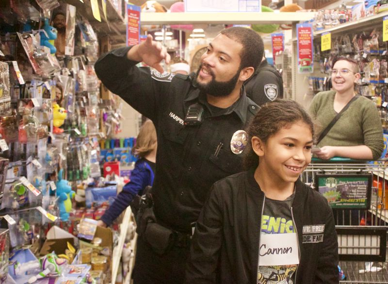 PMG PHOTO: CHRISTOPHER KEIZUR - Officer Walter Harper peruses the toy aisle during the annual Gresham Shop with a Cop.