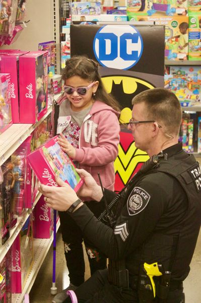 PMG PHOTO: CHRISTOPHER KEIZUR - Sgt. Ted Vanbeek describes Barbie dolls to the girl he explored Fred Meyers with during Shop with a Cop.