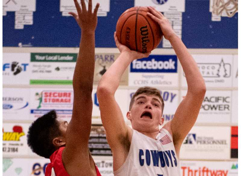 LON AUSTIN/CENTRAL OREGONIAN - Caleb Arnold goes up for two of his 13 points against South Albany on Saturday. Arnold also had 13 points on Friday against North Salem as the Cowboys split the two games.