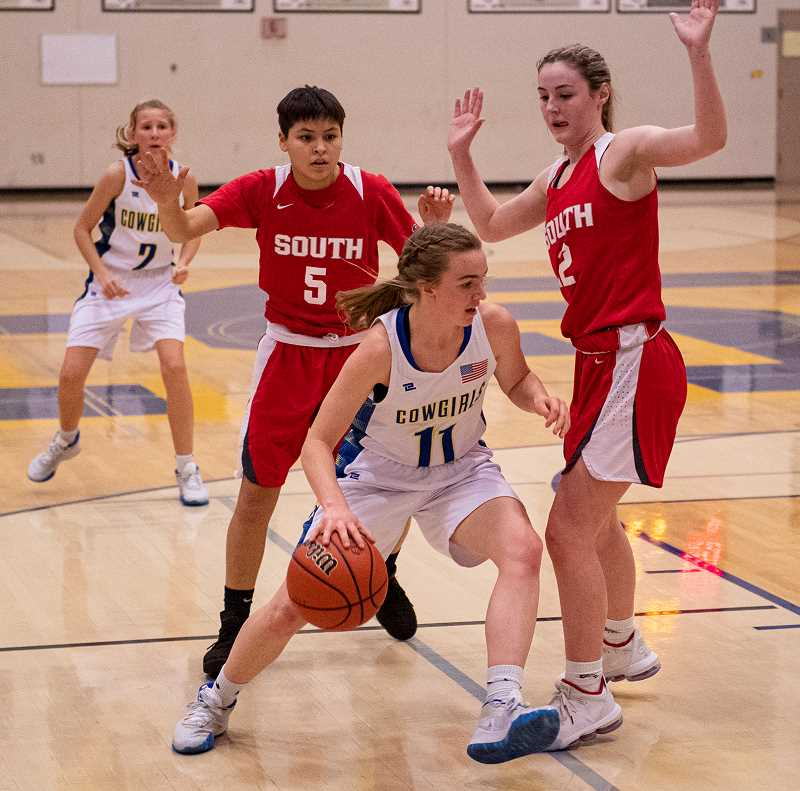 LON AUSTIN/CENTRAL OREGONIAN - Dallas Hutchins drives past Adrianna Whitebird, 5, and Nikilie Robinson, 12, on her way to the basket for two of her eight points against the Redhawks. South Albany won the game 66-43.