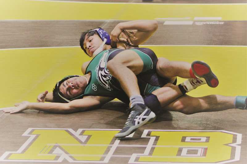 COURTESY PHOTO: WOODBURN WRESTLING - Woodburn's Wesley Vasquez and North Marion's Ronaldo Hernandez square off in the opening round of the 132-pound bracket of the North Bend Coast Classic. Vasquez went on to place second, leading the Bulldogs to a 14th-place finish out of 32 teams over the weekend.