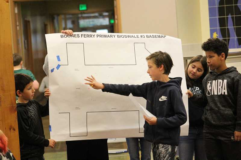 PMG PHOTO: COREY BUCHANAN - From left: Cristian Perde, Liam Kleinke, Abigail Meyer and William Maina give a presentation to the rest of the fifth grade that shows where they would place plants around the school grounds.