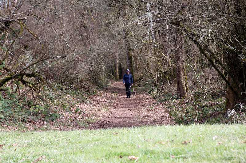 OREGON STATE PARKS - A hiker and his pooch get some fresh air and exercise on a trail at Champoeg State Heritage Area.