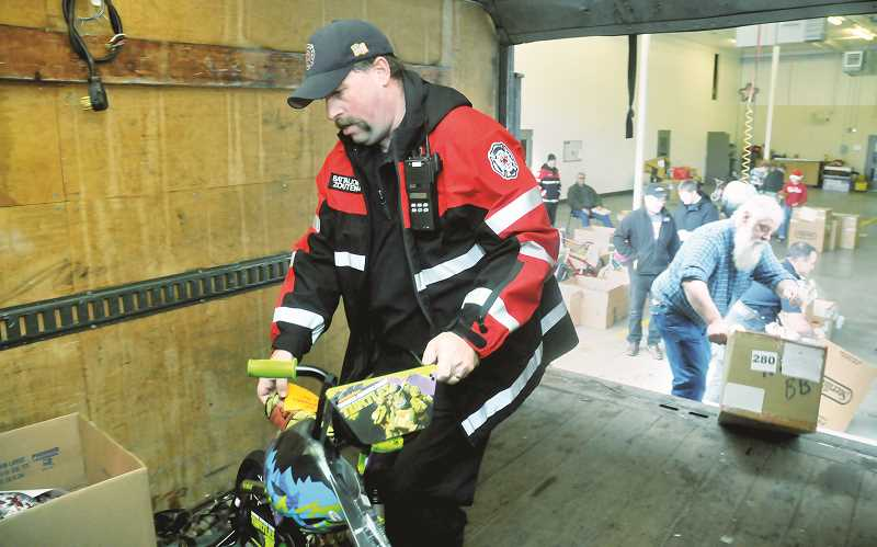 GRAPHIC FILE PHOTO - Dozens of volunteers will assemble at the downtown fire station on Christmas Eve to organize and distribute thousands of toys as part of the Toy and Joy Program in Newberg.