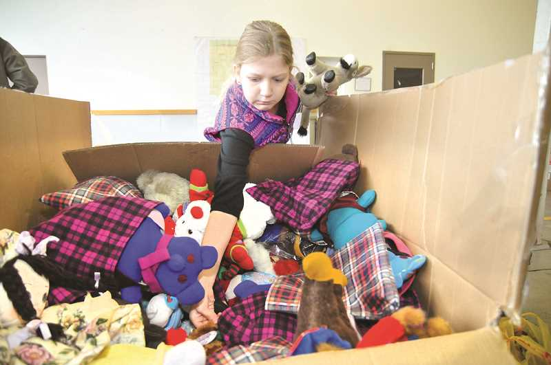 GRAPHIC FILE PHOTO - A young volunteer grabs a plush toy as an additional present for a lucky child on Christmas Eve.