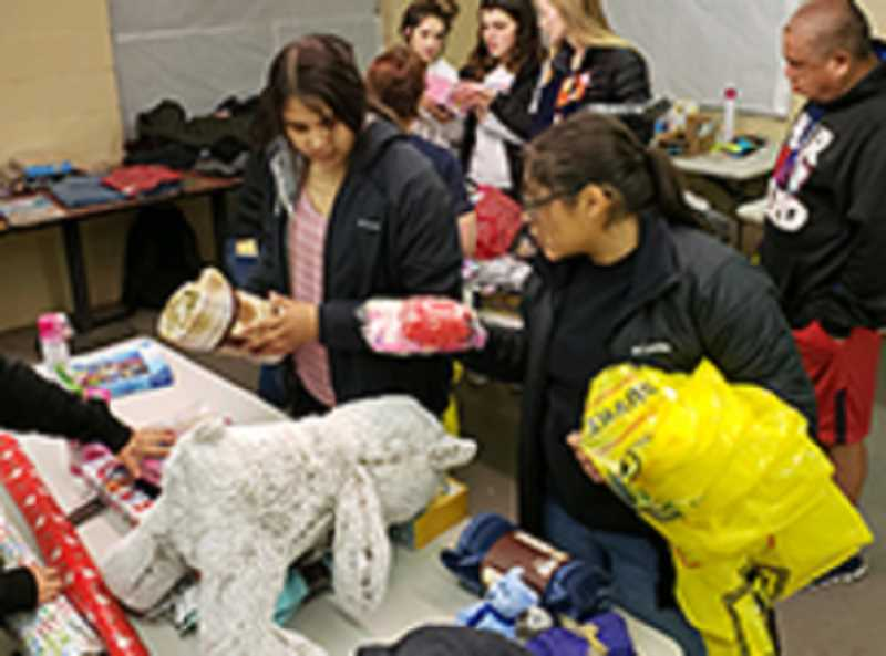 SUBMITTED PHOTO - Volunteers help select gifts and wrap them, as a part of Operation Rudolph, a local program that provides gifts to families that are struggling during the holidays.