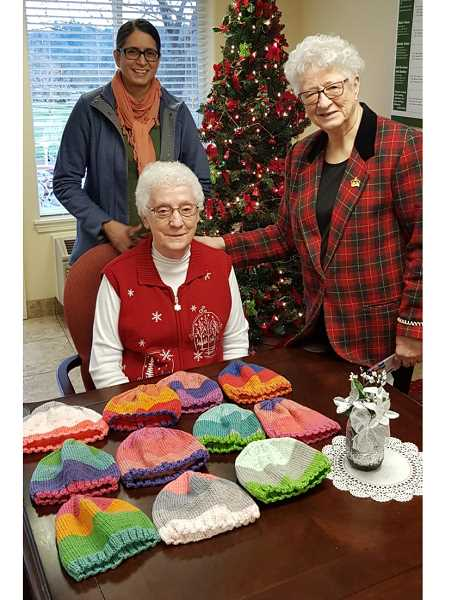 Jenny Sequeira, Dee Wright and Jean Sequeira look over the pile of baby hats in Gladstone ready to send to Africa.